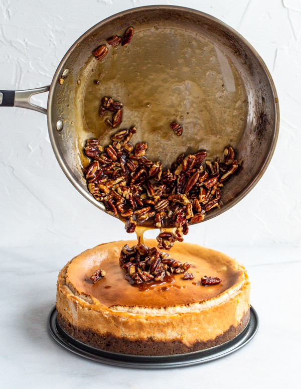Pecan pie filling being poured over cheesecake