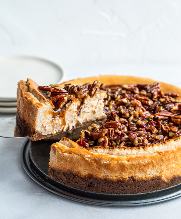 A slice of pecan pie cheesecake being cut out of a big, round cheesecake
