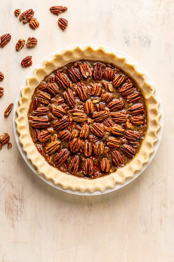 unbaked pecan pie on a cream counter