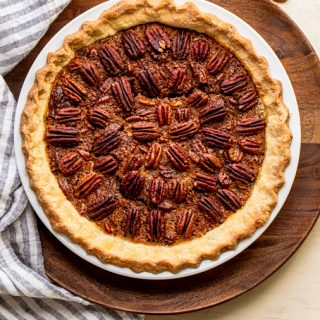 pecan pie in a white pie dish on a wood slab