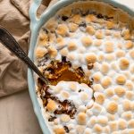 sweet potato casserole with marshmallows and pecans in a blue oval casserole dish with a serving spoon
