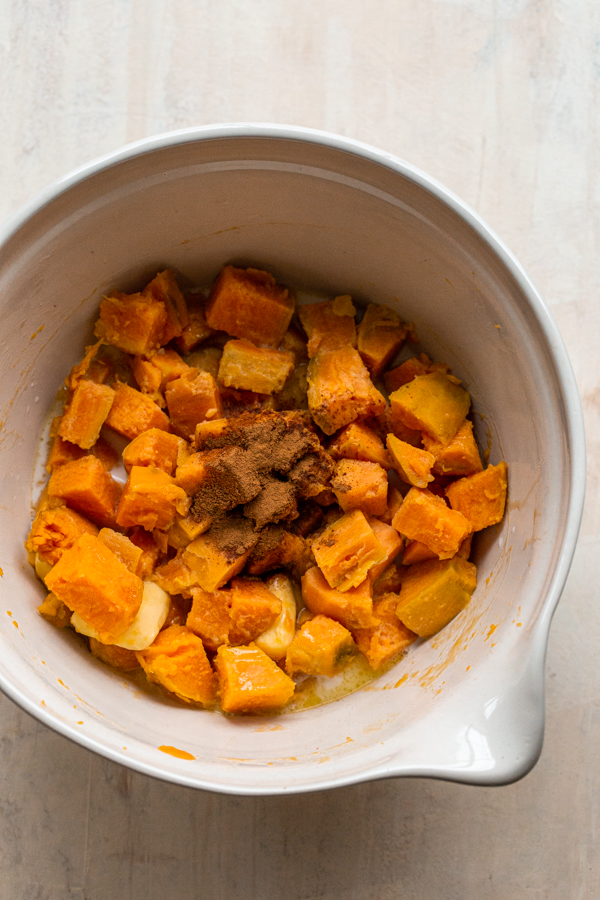 cooked sweet potatoes in a bowl with butter, cinnamon, maple and milk