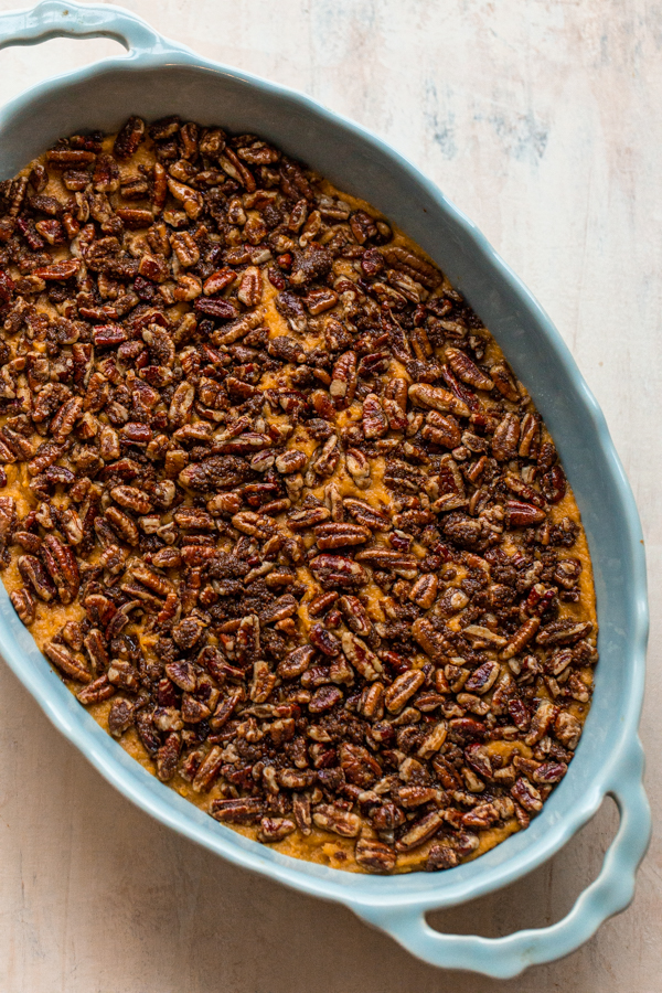 pecans covering whipped sweet potatoes in a blue oval casserole dish