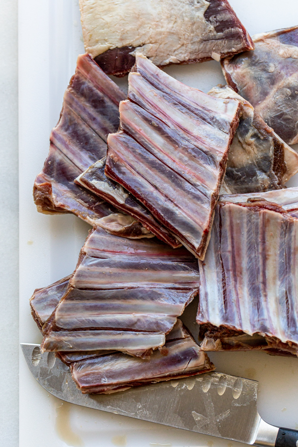raw short ribs from a deer on a white cutting board