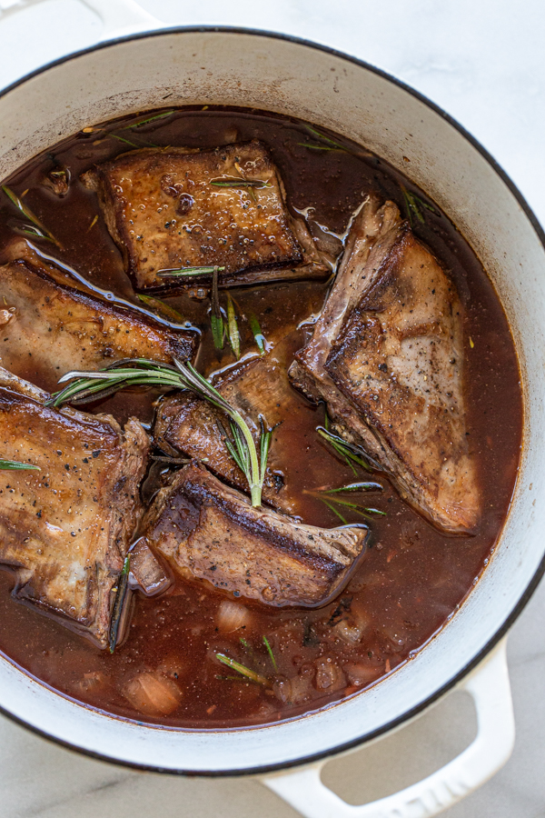 venison short ribs in braising liquid with rosemary sprigs