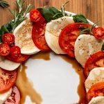 Caprese salad made into a wreath shape on a white plate
