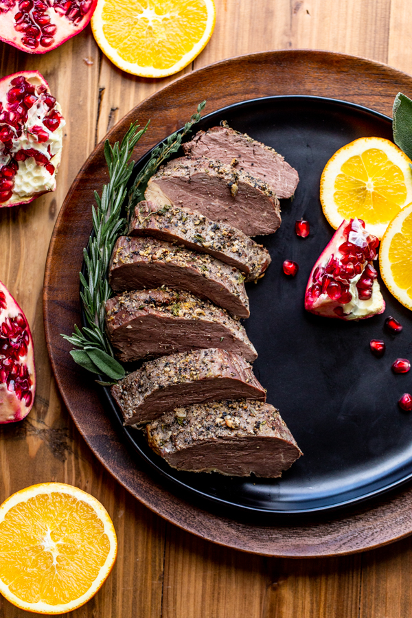sliced bison tenderloin on a black plate with oranges and pomegranates on a wood table