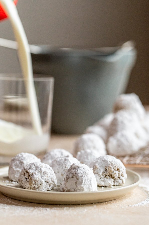milk being poured into a glass behind cookies dusted with powdered sugar