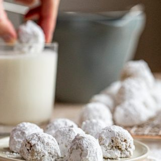 mexican wedding cookies on a plate with one being dunked into a glass of milk