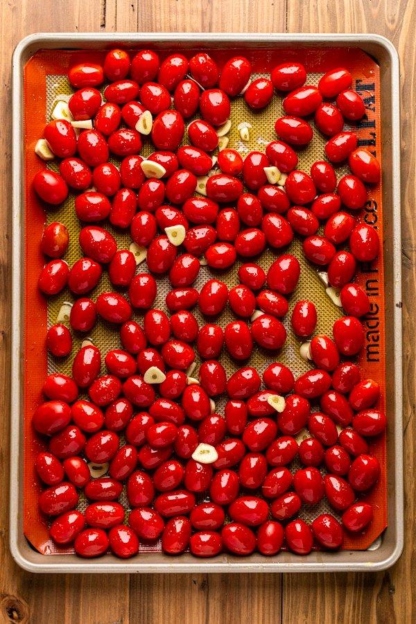 tomatoes and garlic on a baking sheet