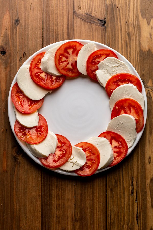 tomatoes and cheese arranged in a circle on a white plate