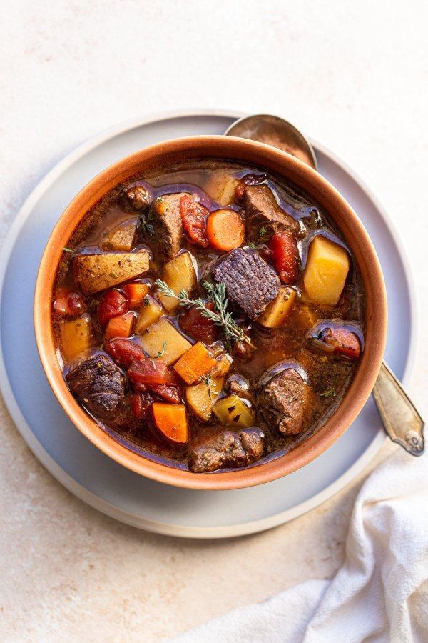 venison stew in a terra-cotta bowl with a thyme leaf