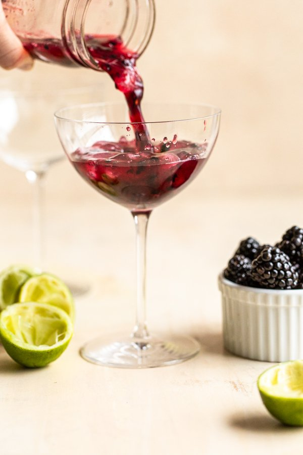 pouring a blackberry drink into a coupe glass