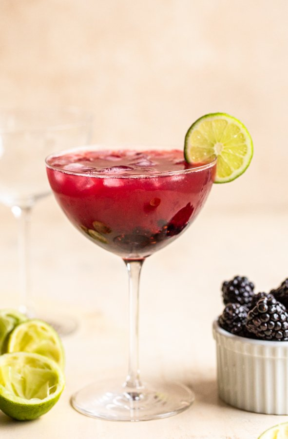 blackberry mockarita in a coupe glass with a lime wedge