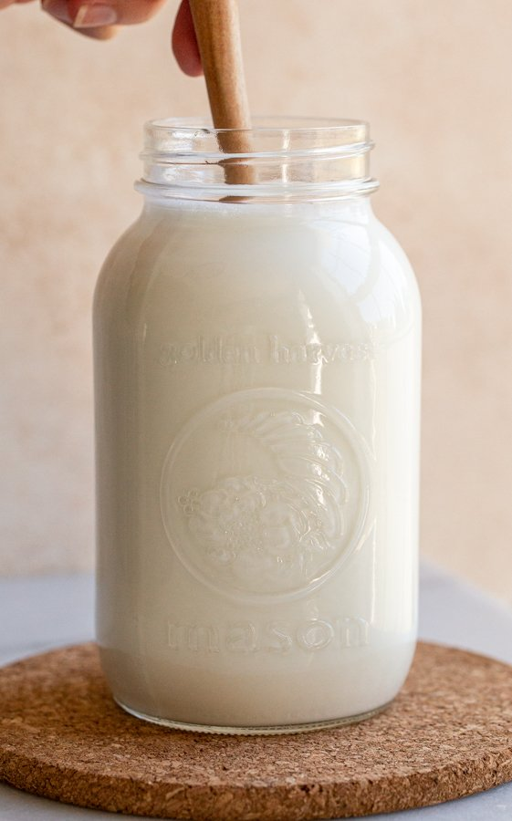 mixing milk in a glass jar with a wood spoon