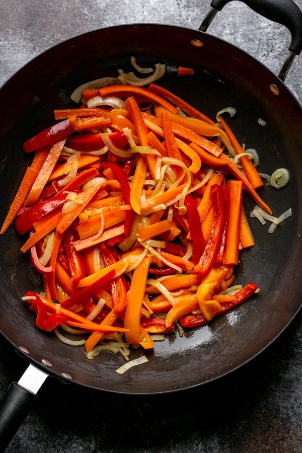 peppers, onions and carrots in a wok