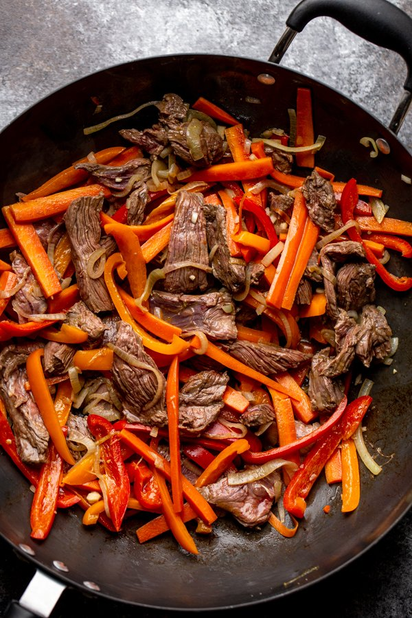 peppers, onions, carrots and venison steak in a wok