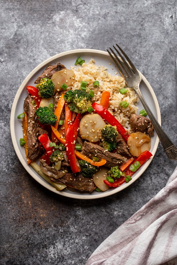 venison stir fry on a light blue plate with a fork
