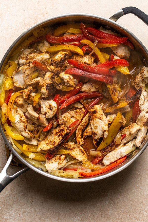 chicken, peppers and onions in a skillet