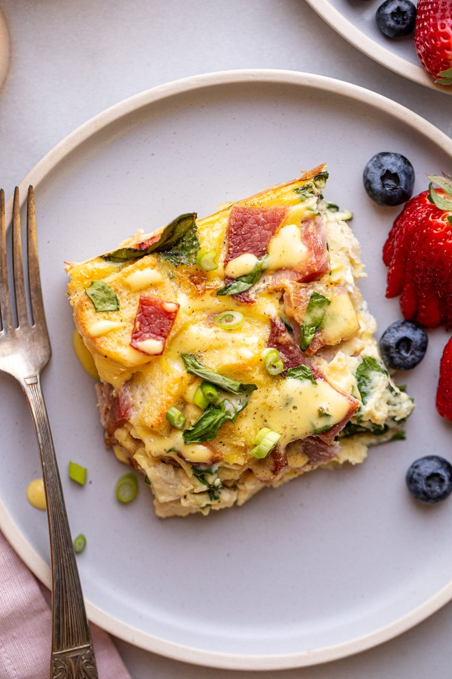 eggs Benedict casserole on a blue plate with fruit