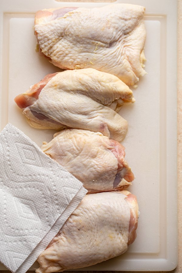 chicken thighs being patted dry on a cutting board