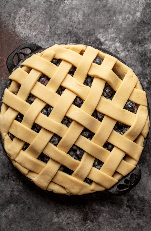 an unbaked lattice top pie on a grey counter