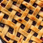 blueberry pie on a grey counter in a black pie dish