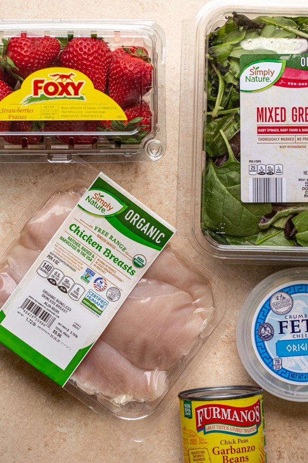 ingredients for grilled chicken and strawberry salad on a cream counter