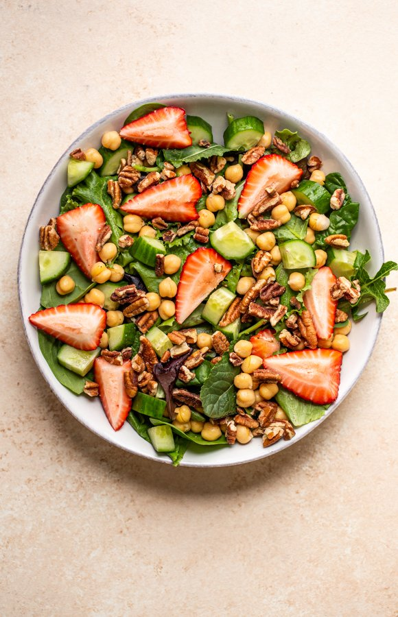 salad in a bowl with chickpeas, pecans and strawberries