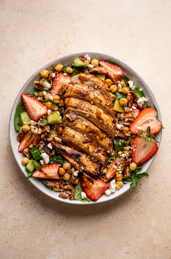 grilled chicken and strawberry salad in a bowl with a fork and a pink napkin