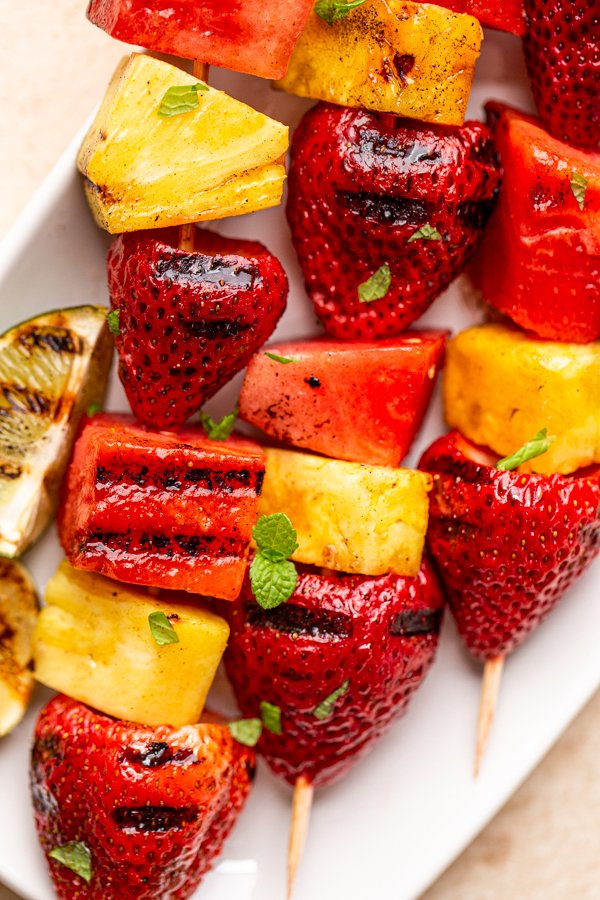 grilled fruit kabobs on a white plate with charred lime