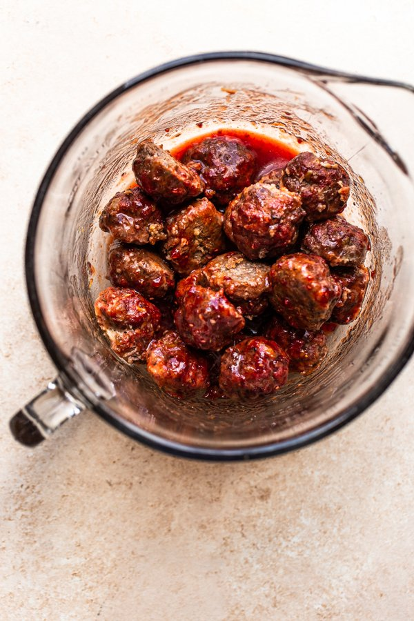 meatballs being tossed in a sauce in a bowl