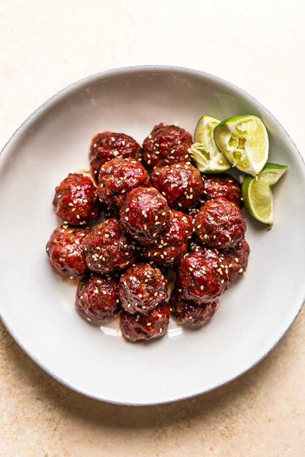 smoked venison meatballs in a white bowl with lime slices