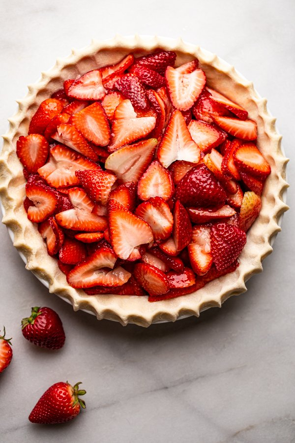 sliced strawberries in a pie dish, unbaked