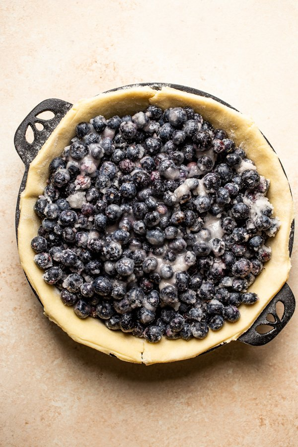 pie crust with blueberries in a cast iron pie plate