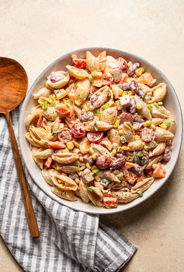 southwest pasta salad in a white bowl with a wood spoon on a cream counter