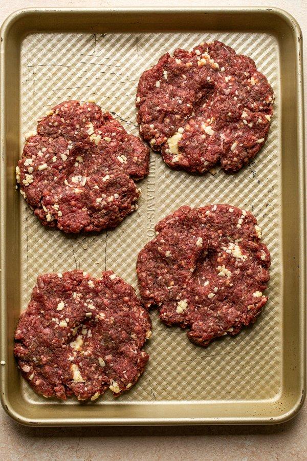 venison burger patties on a baking sheet