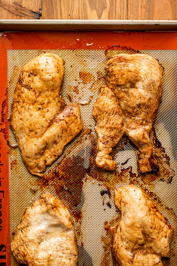 baked chicken on a baking sheet lined with a silpat
