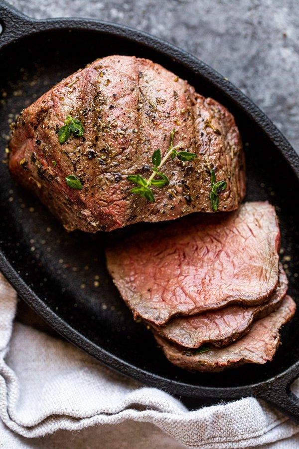 sliced venison steak on a black plate with a napkin