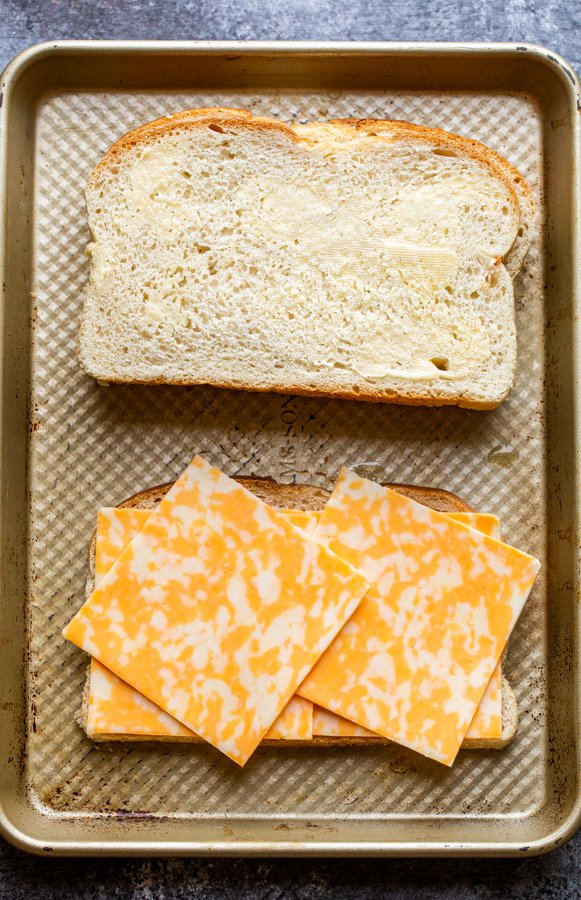 buttered bread and cheese slices on a baking sheet