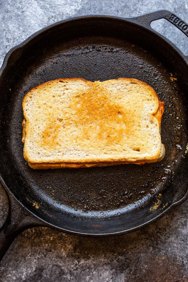 a grilled cheese cooking in a cast iron skillet