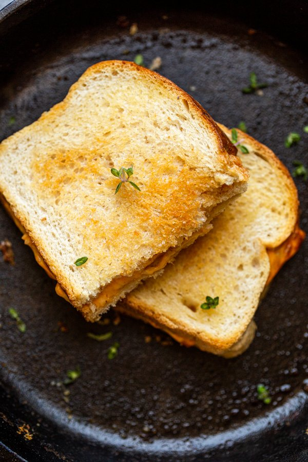 grilled cheese on a black skillet with thyme leaves