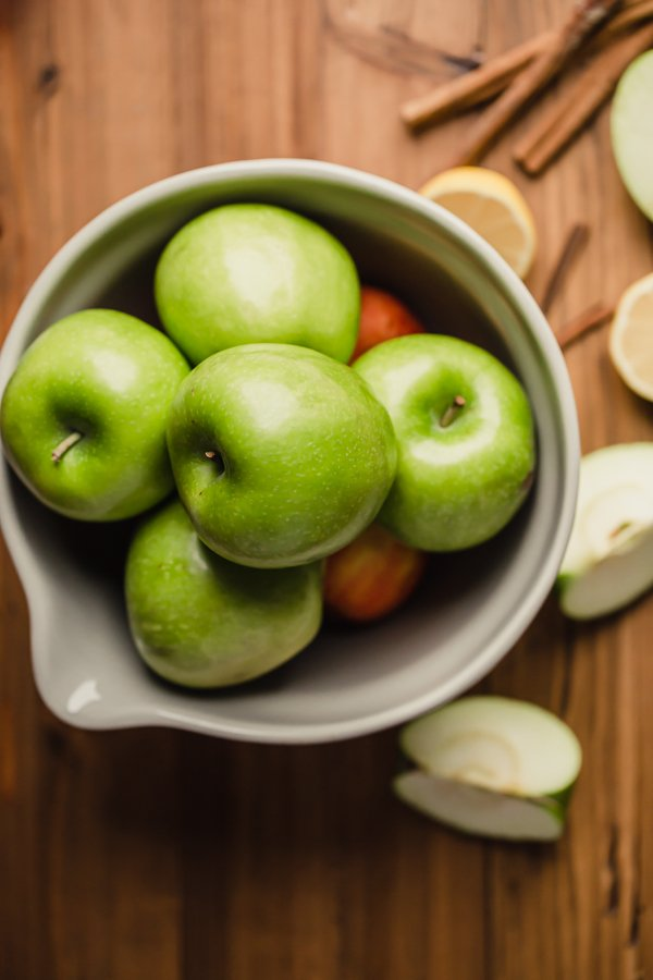 apples in a bowl on a wood counter
