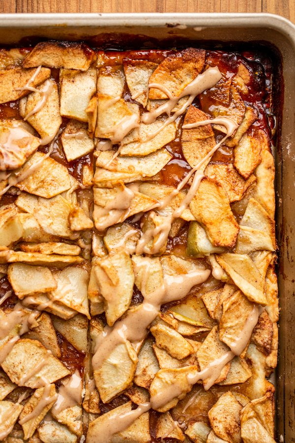 apple pie bars cut into squares in a baking sheet