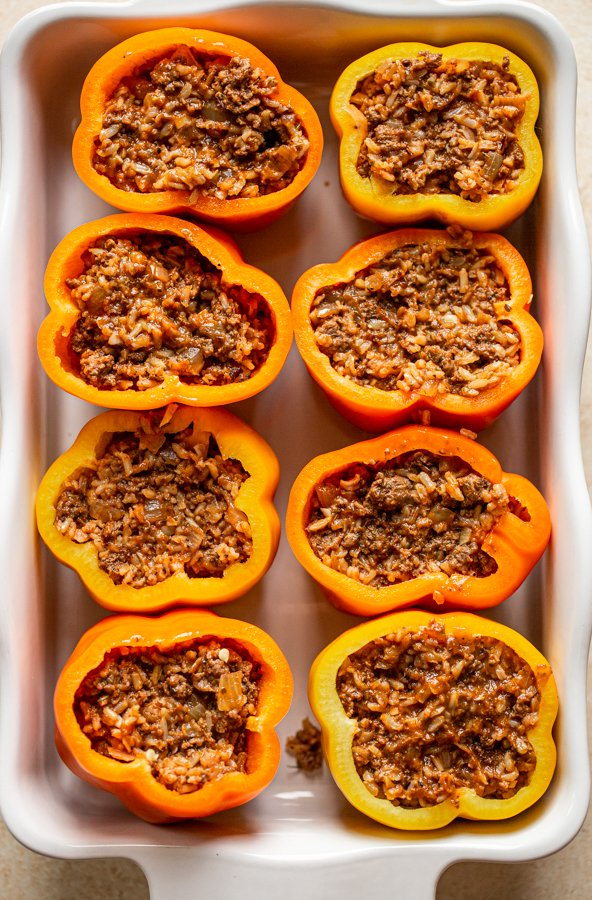 prepping stuffed peppers in a white baking dish