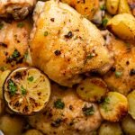 a chicken thigh roasted with potatoes and lemon