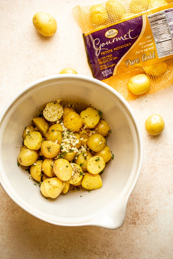 potatoes in a bowl with garlic and herbs