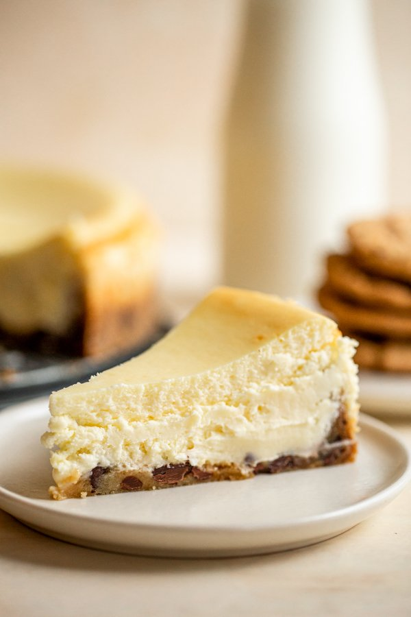 chocolate chip cookie crust cheesecake slice on a white plate