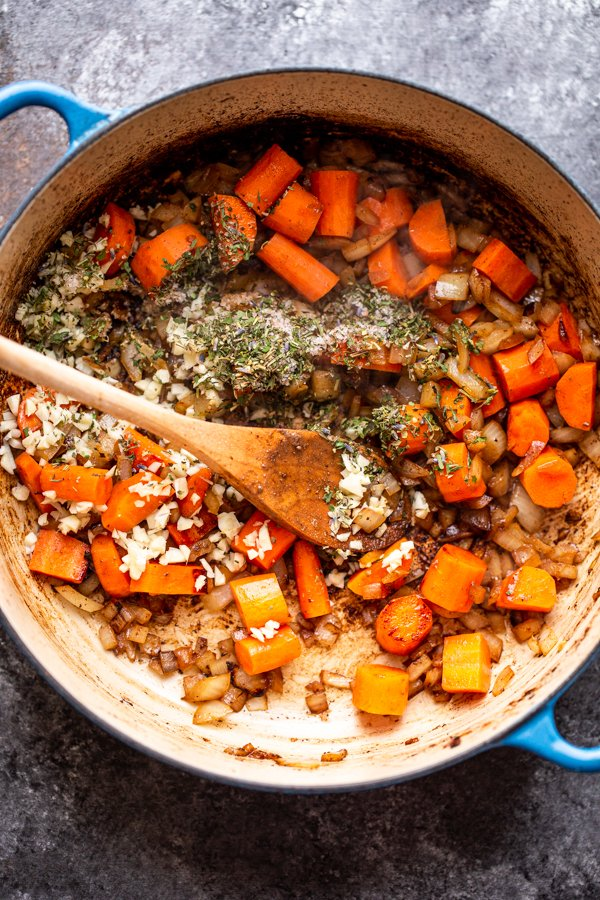 carrots, garlic and herbs in a pot
