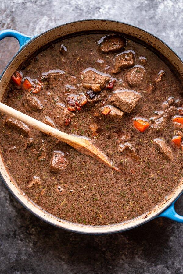 venison bourguignon in a pot before simmering